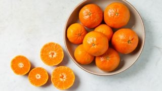 A bowl of fresh whole and halved clementines on a white background