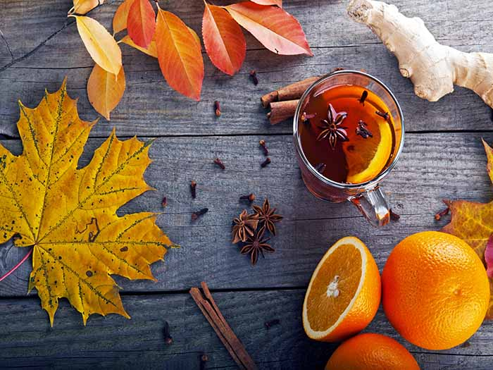 Oranges and cloves on a black counter with autumn leaves next to a clove tea cup