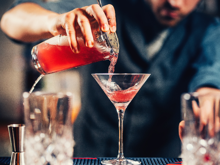 Barman pouring cocktail into a martini glass
