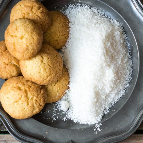 Coconut cookies kept next to coconut flour, on a steel plate.