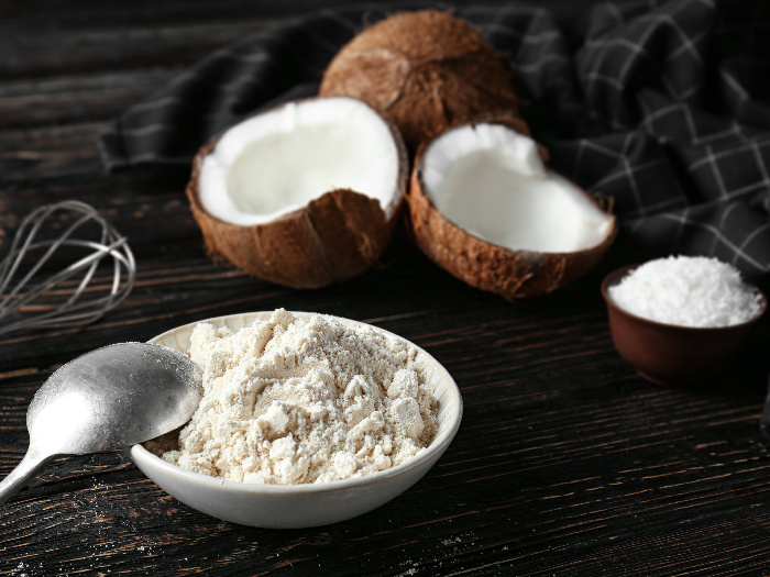 A bowl full of coconut flour kept next to coconuts atop a black platform