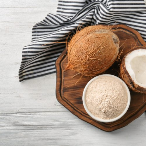 Coconuts and a bowl of coconut flour on a wooden board with a black & white striped napkin.