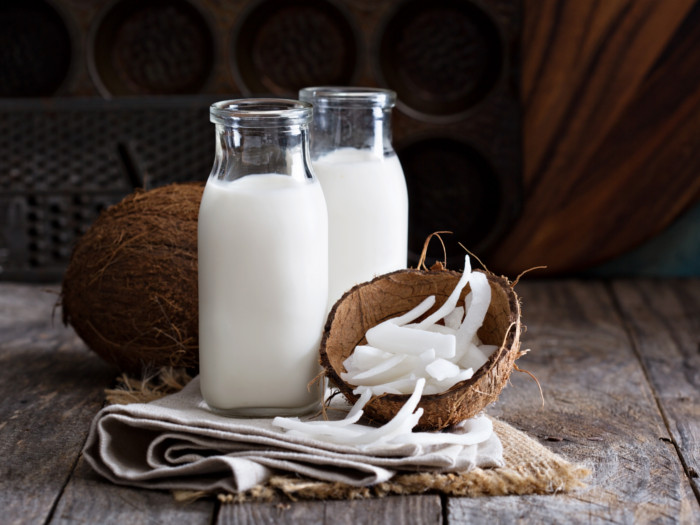 Glass bottles of coconut milk, whole coconut, and shelled coconut meat