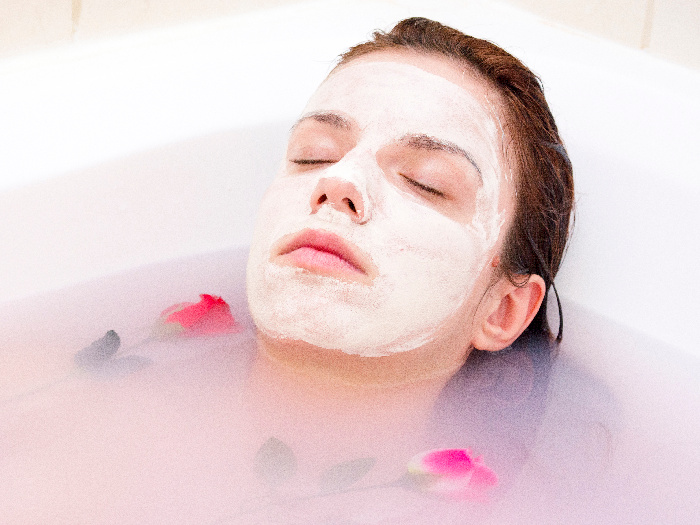 A woman enjoying a soothing bath after having applied a face mask