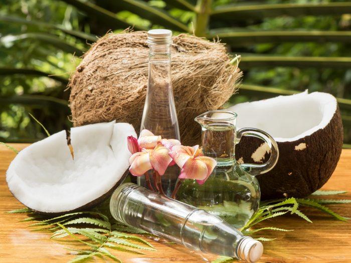 背景をぼかした木製のテーブルの上に、半分と全部のココナッツが入ったココナッツオイルのボトル