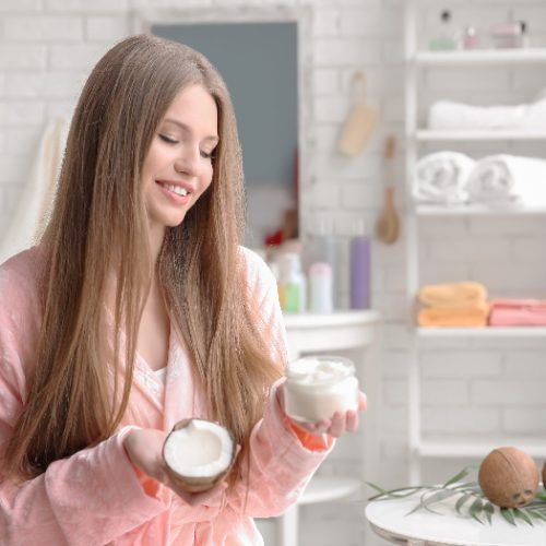 A woman with long hair in the bathroom holding a coconut and a hair mask bottle