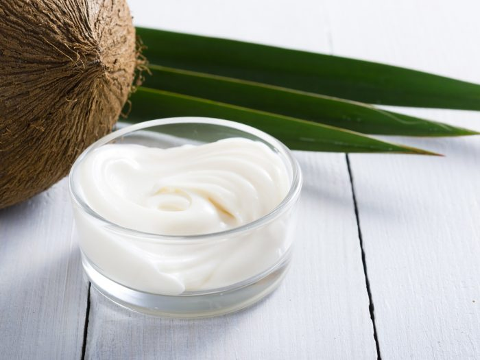A lotion made from coconut oil in a bowl, with a coconut in the background