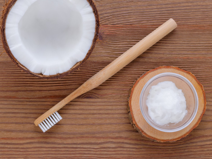 Flatlay view of a wood toothbrush placed in between a bowl of coconut cream and a coconut half.