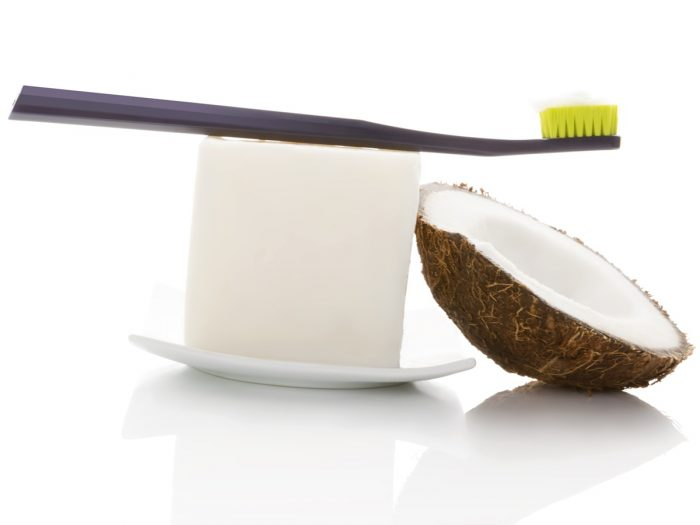 A coconut shell placed alongside a white bar with a toothbrush placed on top of a white dish with a white background.