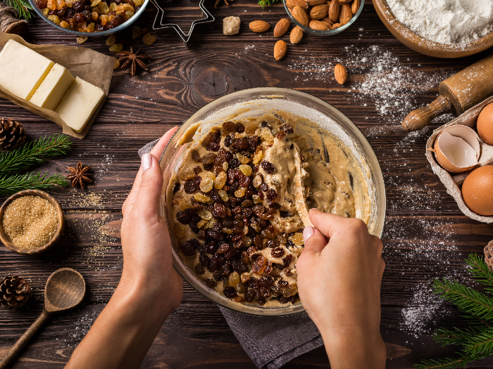 A top view picture of a young woman's hand mixing ingredients for baking a christmas fruit cake.