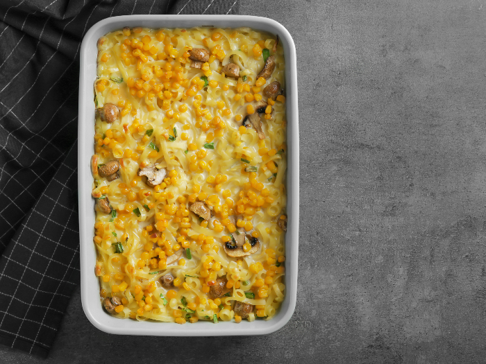 A flatlay pic of tasty casserole with corn in a baking dish