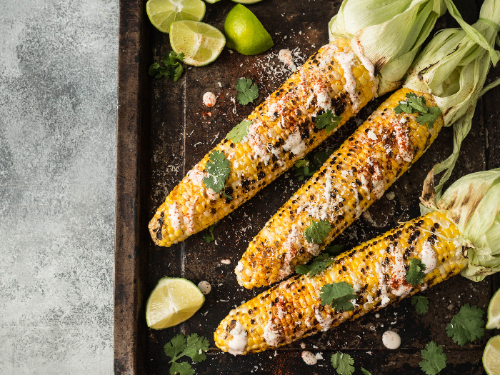 A flat lay picture of grilled corn cobs with sauce, coriander, lime, paprika and cheese.