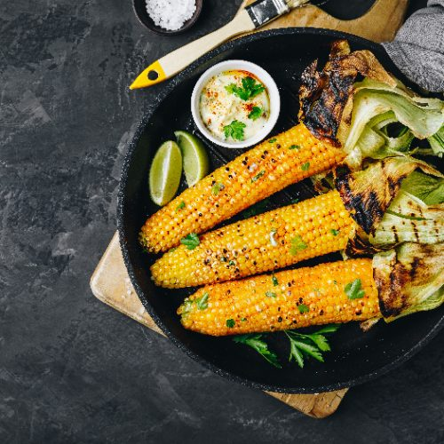 A top view picture of roasted or grilled sweet corn cobs with garlic butter and lime placed on dark gray stone background