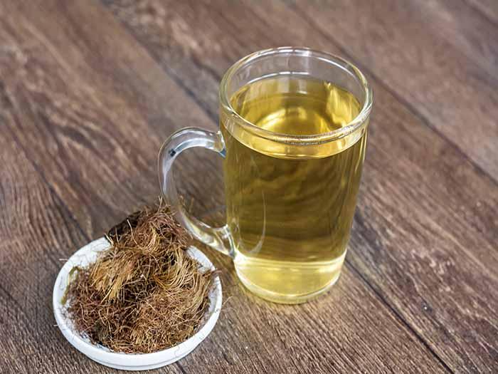 A cup of corn silk tea kept beside a bunch of corn silk on top of a wooden platform