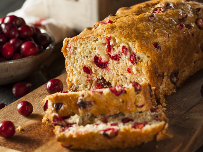 Cranberry bread loaf with a couple of slices next to cranberries on a counter