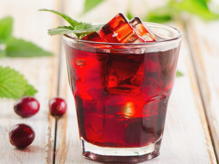 A glass of red-colored liquid in a glass-topped with ice and a sprig of mint on a wooden surface