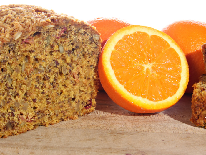 cranberry orange bread next to a halved orange on a counter