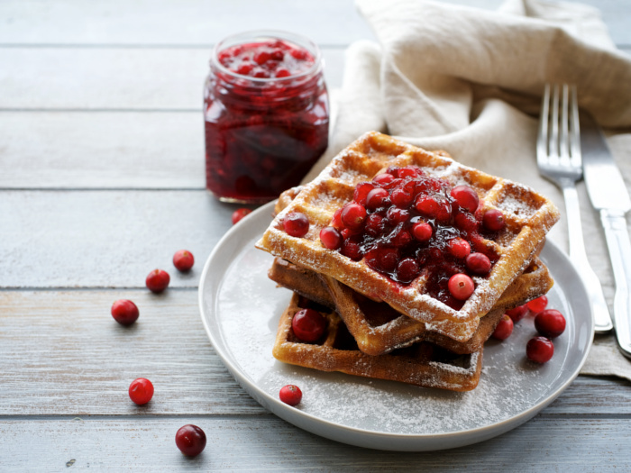 cranberry sauce in a glass jar next to a plate with waffles and cranberry sauce on a wooden table