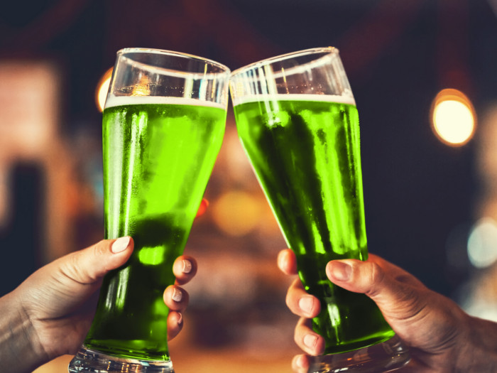 Two hands clinking glasses containing a green liquid.