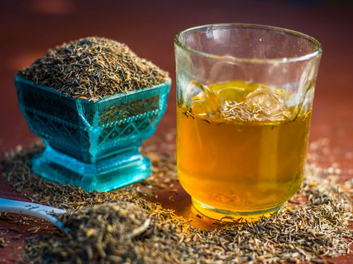 A glass of cumin water and a bowl of cumin seeds
