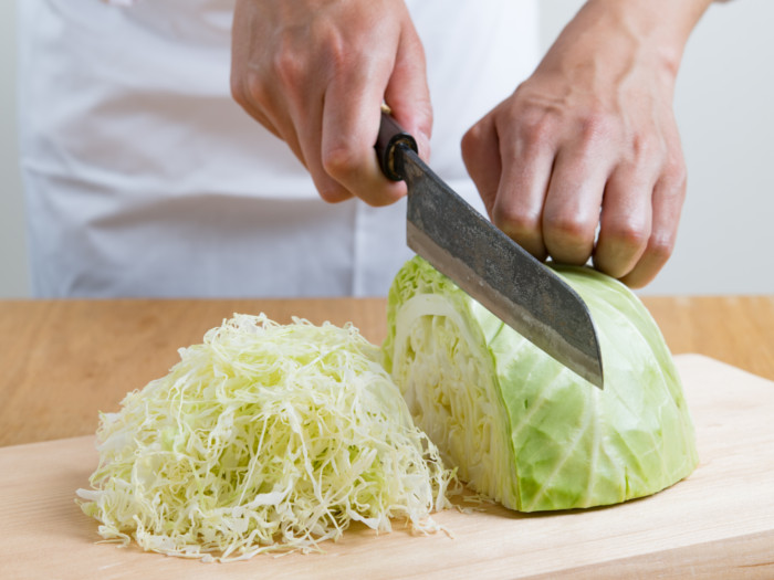 Cabbage being cut with a knife