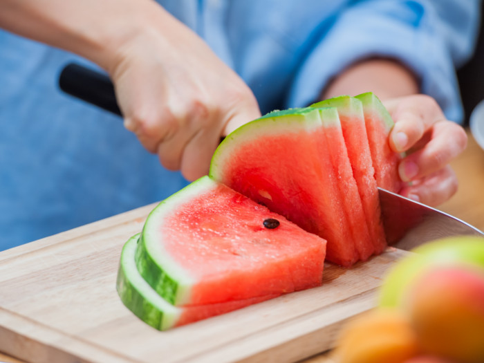 Close up of a person cutting a watermelon