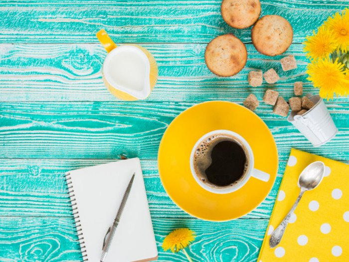 A cup of dandelion coffee next to sugar cubes, a cream jug, muffins, and a journal on a blue counter