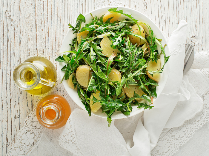 Healthy dandelion green salad with potatoes in a bowl with salad dressings