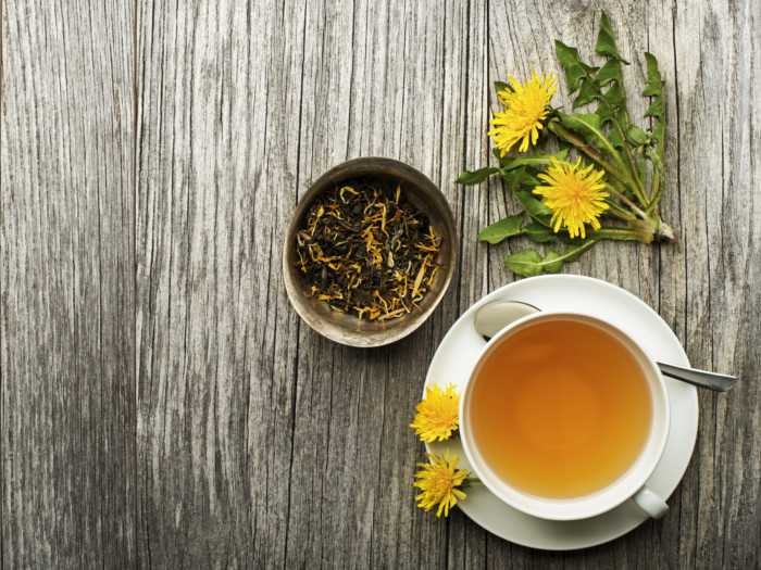 A cup of dandelion tea, some dandelion flowers and dried dandelion loose leaf tea on a table