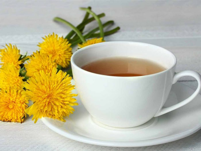 A cup of dandelion tea with flowers on a white wooden table