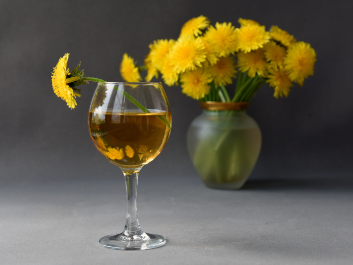 A close up picture of a glass of dandelion wine kept atop a table