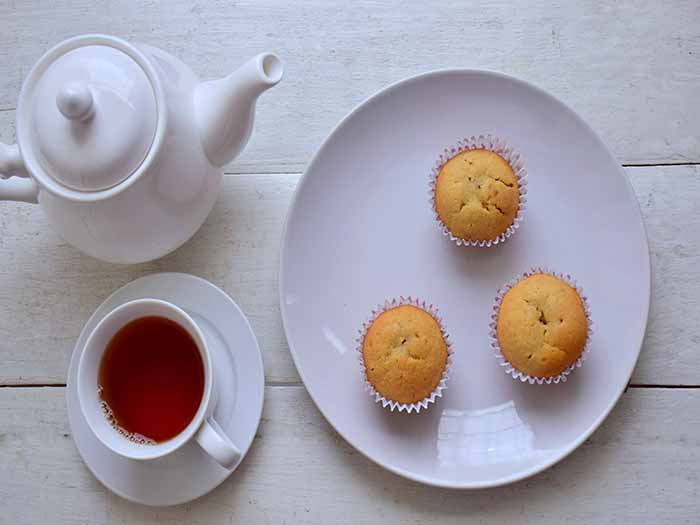 Flatlay picture of a pot of tea, cup and saucer of tea with a plate containing three cupcakes on a white wooden surface