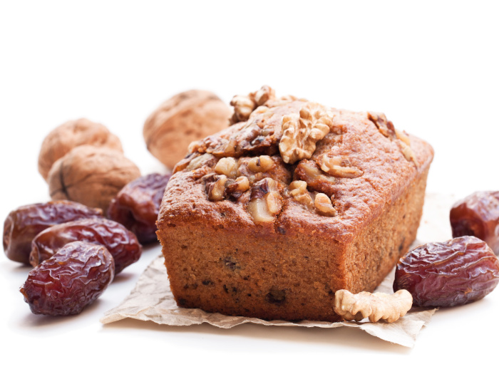Homemade date and walnut loaf cake isolated on white background