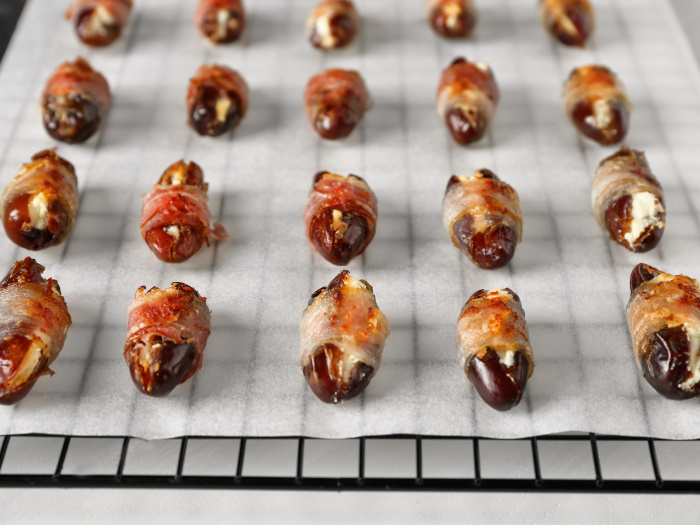 Dried dates wrapped in bacon set on a baking rack