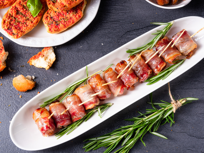 Bacon-wrapped dates served on a white tapas plate with rosemary