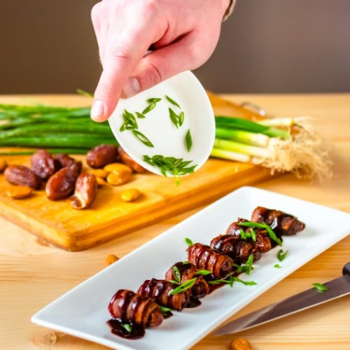Close up on a hand putting sliced green onions on dates wrapped in bacon