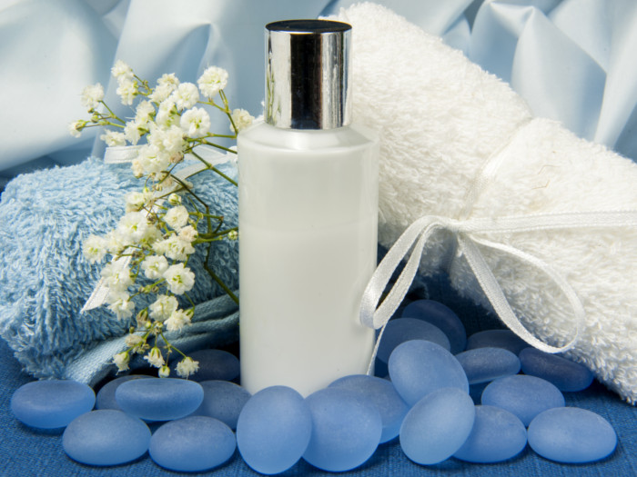 White bottle placed behind blue pebbles with white and blue towels placed at the back