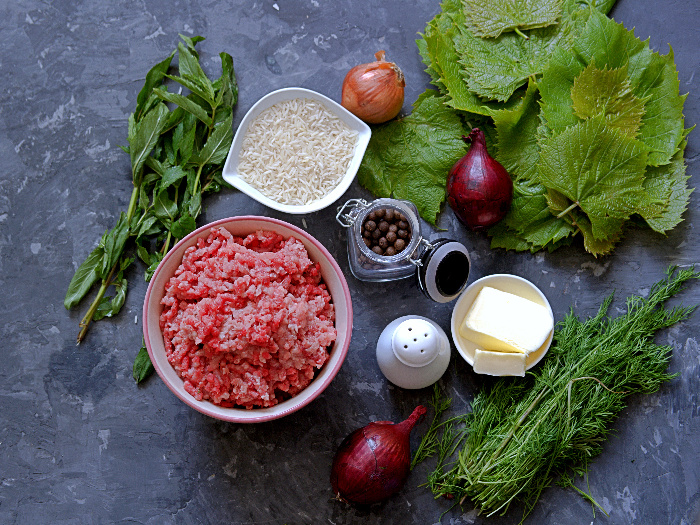 Ingredients for cooking dolma (minced meat, fresh grape leaves, butter, rice, mint, onion, dill, spices)