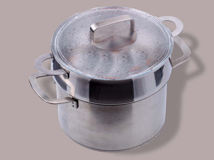 A double boiler on a light lavender-colored background.