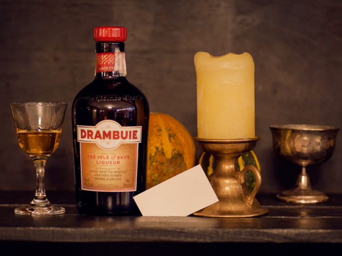 A bottle of Drambuie next to a glass filled with it and a candle