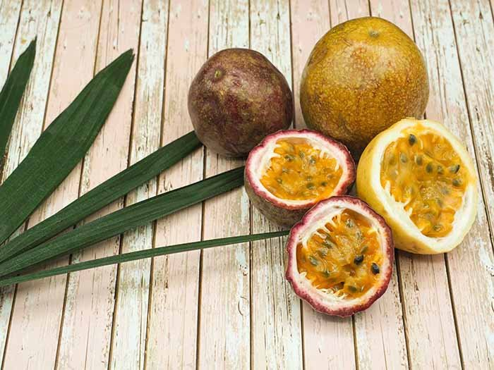 Whole and sliced passion fruit with leaves on a light wooden table
