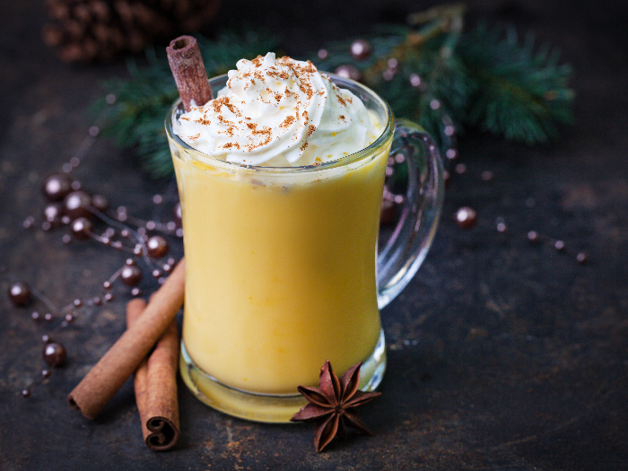 Eggnog topped with whipped cream and stick of cinnamon