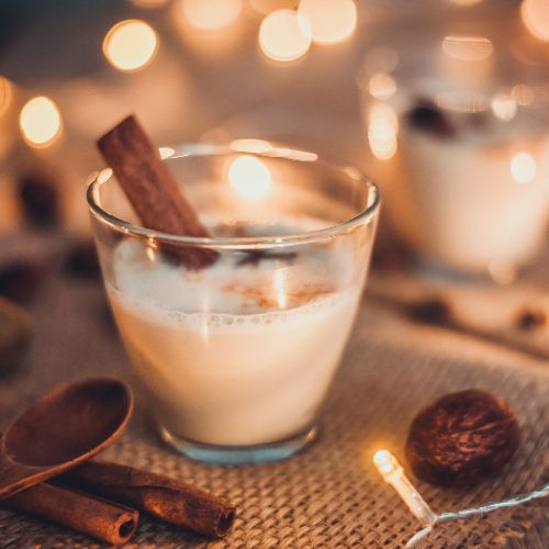 Eggnog in glasses with star anise and cinnamon on wooden table for Christmas and winter holidays