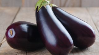 A close-up view of fresh eggplants placed on a wooden table