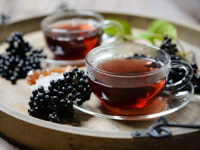 Cups of elderberry tea with fresh elderberries on a wooden table