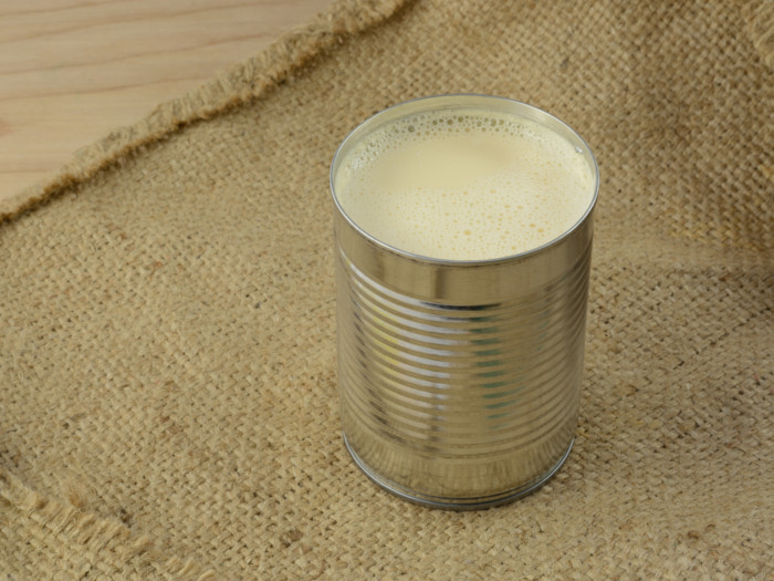 Open tin of evaporated milk placed on burlap cloth.