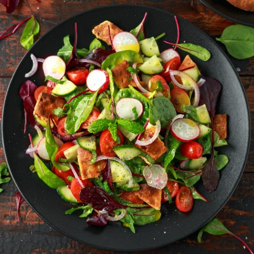 Traditional fattoush salad on a plate with pita croutons, cucumber, tomato, red onion, vegetables mix and herbs