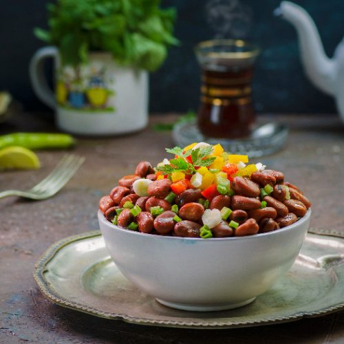 fava bean salad in a white bowl on a platter
