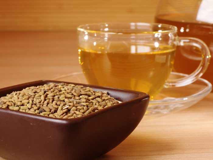 A bowl of fenugreek seeds with a cup of tea on a wooden table