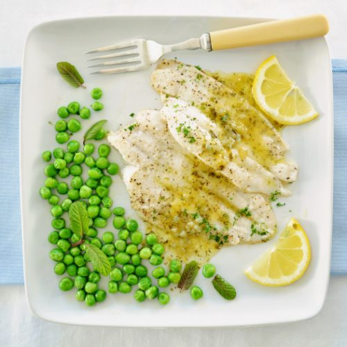 A top view of fish fillets drizzled with lemon butter sauce and organic minty peas